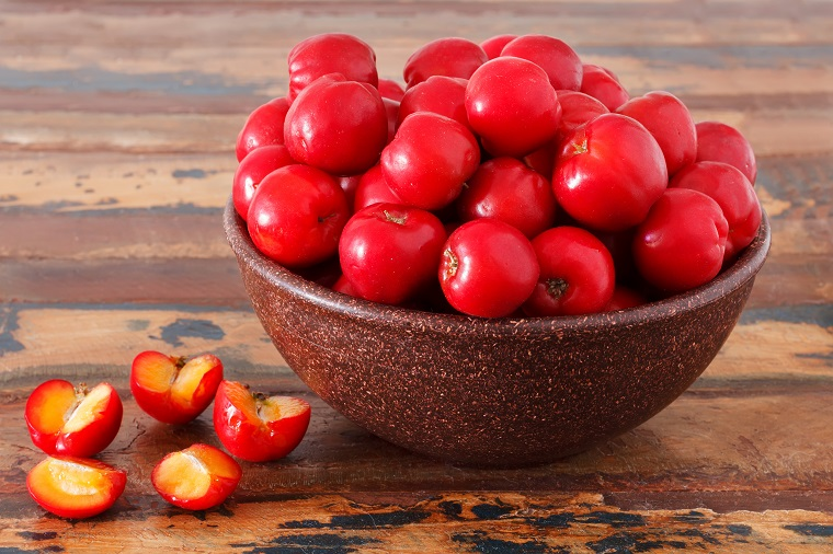 Malpighia glabra (red acerola), tropical fruit  on wooden table. Selective focus